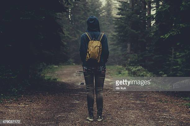 Traveler with backpack walking in a foggy forest