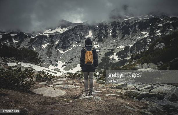 Traveler with backpack walking in a misty mountains