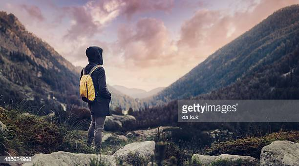 Traveler with backpack walking in mountains in the evening