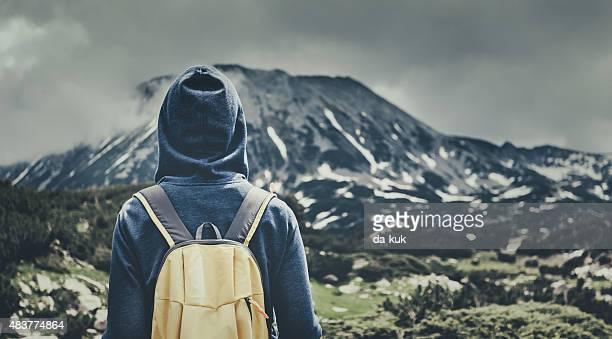 Reisende mit Rucksack zu Fuß in den Bergen