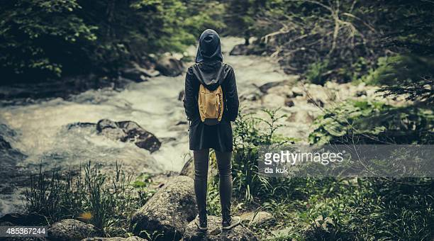 Traveler with backpack walking near mountain river in forest