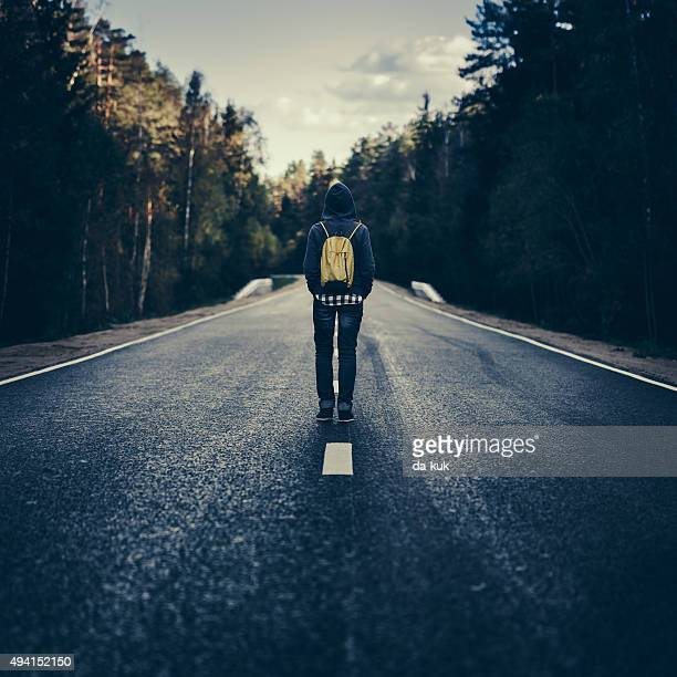 Traveler with backpack walking on the road