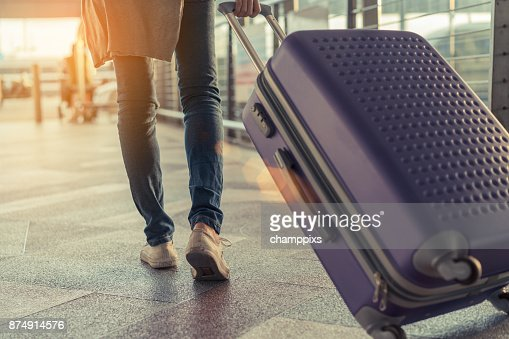 Traveler with suitcase in airport concept.Young girl  walking with carrying luggage and passenger for tour travel booking ticket flight at international vacation time in holiday rest and relaxation. : Foto stock