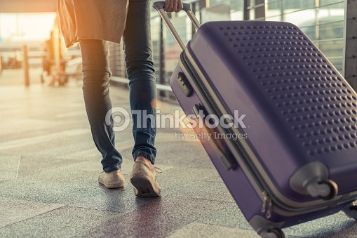 Traveler with suitcase in airport concept.Young girl  walking with carrying luggage and passenger for tour travel booking ticket flight at international vacation time in holiday rest and relaxation. : Foto de stock