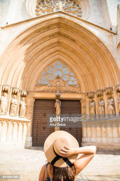 Traveler woman contemplating the cathedral of Tarragona looking up and holding hat during summer vacations in the Catalonia region.