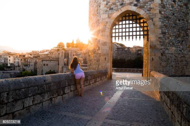 Traveler woman contemplating the city from the old bridge of Besalu town during travel vacations in the Catalonia region with nice sunset warm light.