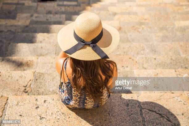 Traveler woman contemplating the old town of Tarragona from stairs during summer vacations in the Catalonia region.