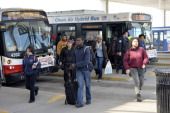 Travelers and commuters arrive at the Chicago Transit Authority's Rosemont station on shuttle busses after a train derailment shut down the CTA's...