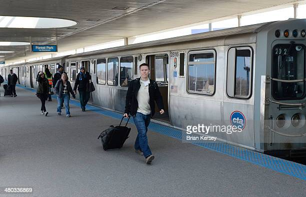 Travelers and commuters arrive at the Chicago Transit Authority's Rosemont station and head towards shuttle busses after a train derailment shut down...