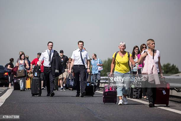 Travelers and flight crew walk with their luggage on a road near Charles de Gaulle airport as French cab drivers block roads and protest against Uber...