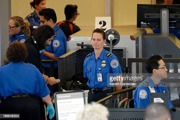 Travelers are screened by Transportation Security Administration agents after Terminal 3 was reopened a day after a shooting at Los Angeles...