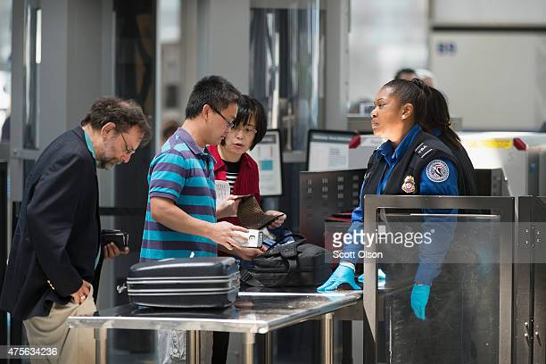 Travelers are screened by Transportation Security Administration workers at a security check point at O'Hare Airport on June 2 2015 in Chicago...