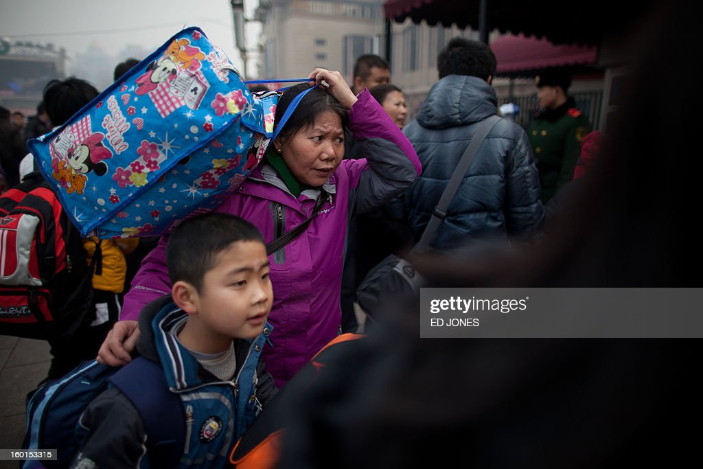 Travelers arrive at Beijing Railway Station in Beijing on January 27, 2013. The world's largest annual migration began in China with tens of thousands in the capital boarding trains to journey home for next month's Lunar New Year celebrations. AFP PHOTO / Ed Jones