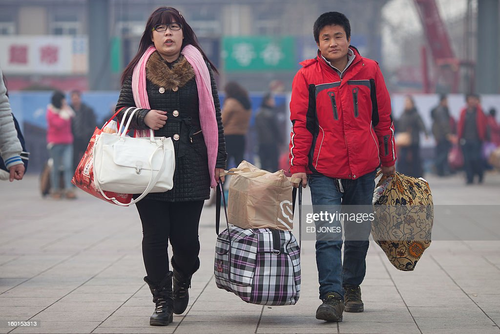 Travelers arrive with their luggage at Beijing Railway Station in Beijing on January 27, 2013. The world's largest annual migration began in China with tens of thousands in the capital boarding trains to journey home for next month's Lunar New Year celebrations. AFP PHOTO / Ed Jones