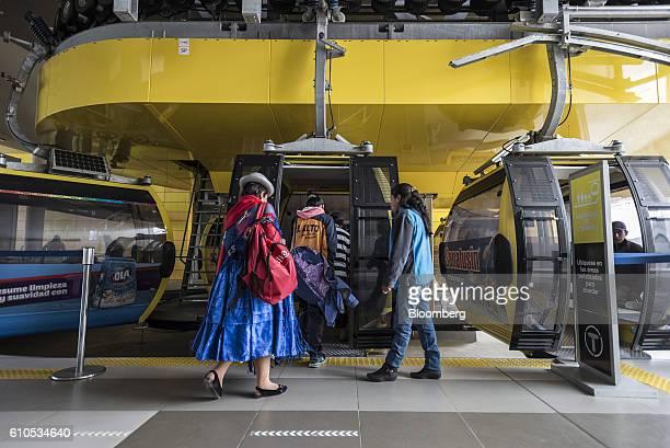 Travelers board a yellow line Mi Teleferico cable car in El Alto Bolivia on Sunday Sept 4 2016 Boliva's Mi Teleferico cable cars are the longest...