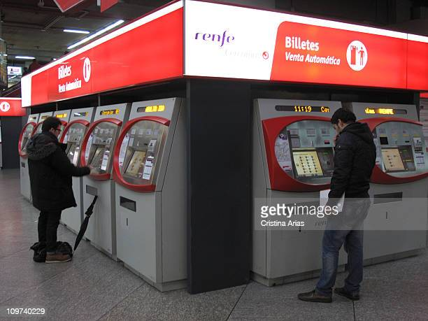 Travelers buying the train ticket in vending machines at the Atocha train station Madrid Spain january 2011