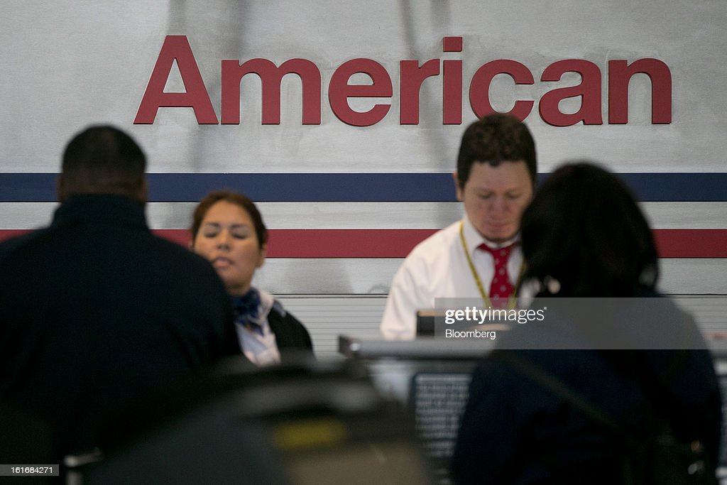 Travelers check in at AMR Corp.'s American Airlines counter at Reagan National Airport in Washington, D.C., U.S., on Thursday, Feb. 14, 2013. US Airways Group Inc., spurned in three prior merger attempts, will combine with bankrupt AMR Corp.'s American Airlines in an $11 billion deal to create the world's largest carrier. Photographer: Andrew Harrer/Bloomberg via Getty Images