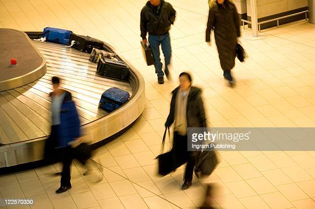 Travelers collecting luggage from airport baggage carousel.