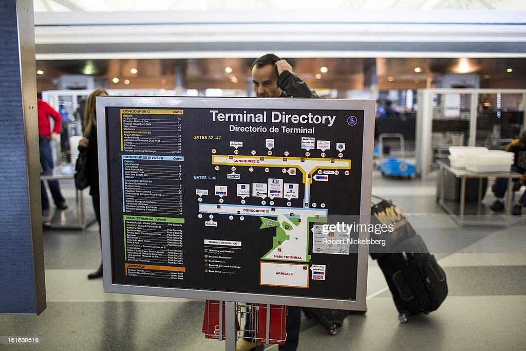 Travelers consult an airport map and terminal directory February 3, 2013 at the John F Kennedy International Airport in the Queens borough of New York.