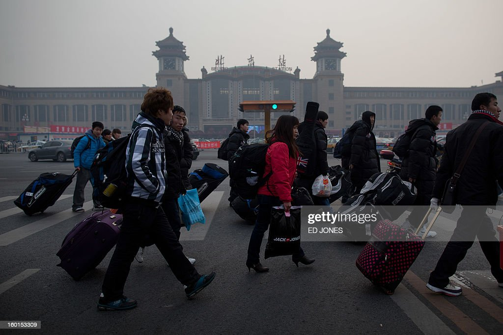Travelers cross a road before Beijing Railway Station in Beijing on January 27, 2013. The world's largest annual migration began in China with tens of thousands in the capital boarding trains to journey home for next month's Lunar New Year celebrations. AFP PHOTO / Ed Jones