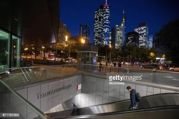 Travelers descend an escalator into Taunusanlage SBahn underground railway station as skyscrapers stand illuminated beyond in the financial district...