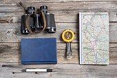 Traveler's equipment include map binocullars notebook pen and compass