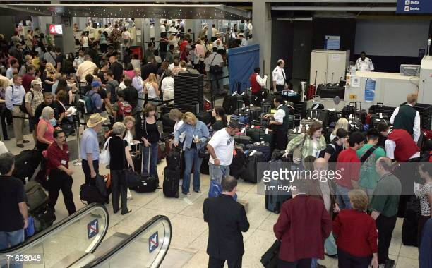 Travelers gather near a near a luggage security screening area right and a security checkpoint top left in Terminal 3 at O'Hare International Airport...