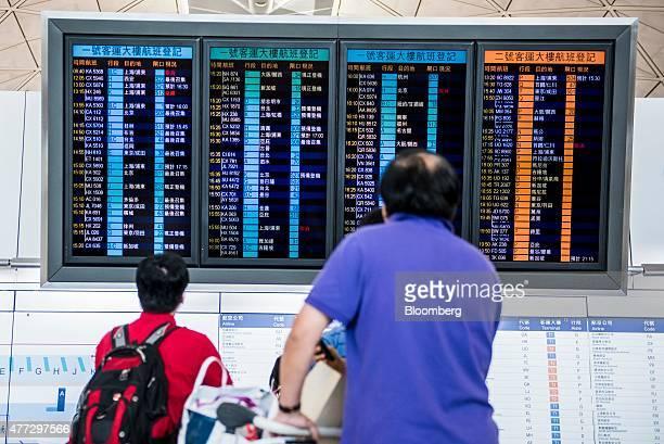 Travelers look at a flight information panel at Hong Kong International Airport in Hong Kong China on Monday June 15 2015 The Hong Kong government in...