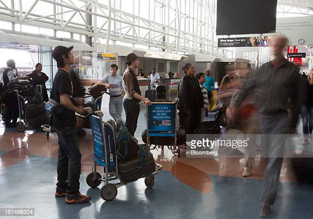 Travelers look at flight information displays at Auckland International Airport in Auckland New Zealand on Tuesday Dec 4 2012 Auckland International...