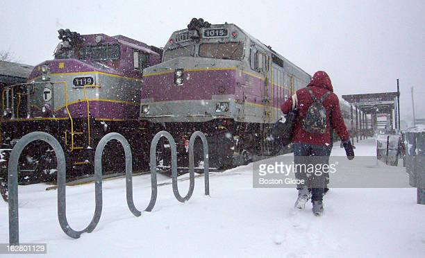 Travelers make their way through swirling snow to catch the MBTA's noon train to Boston at the Rockport Mass station Feb 17 2013 The train left on...