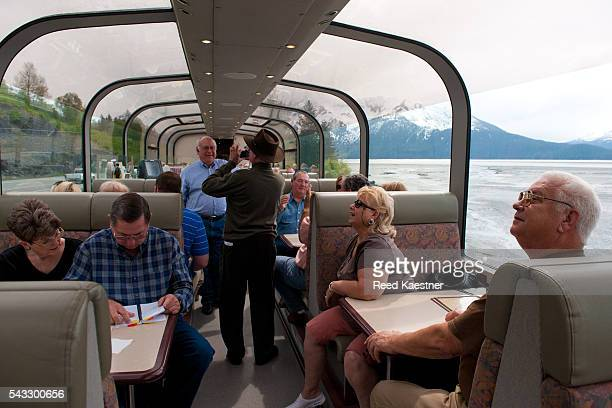 Travelers on the train enjoy the view on the way from Anchorage to Seward Alaska