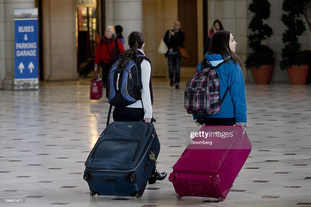 Travelers pull luggage while arriving Union Station in Washington, D.C., U.S., on Wednesday, Nov. 21, 2012. U.S. travel during the Thanksgiving holiday weekend will rise a fourth straight year, gaining 0.7 percent from 2011, as trips by automobile rise even as airplane trips decline, AAA said last week. Photographer: Andrew Harrer/Bloomberg