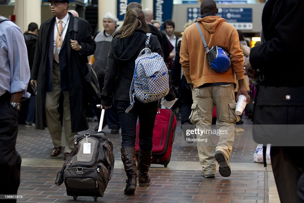 Travelers pull luggage while heading to trains at Union Station in Washington, D.C., U.S., on Wednesday, Nov. 21, 2012. U.S. travel during the Thanksgiving holiday weekend will rise a fourth straight year, gaining 0.7 percent from 2011, as trips by automobile rise even as airplane trips decline, AAA said last week. Photographer: Andrew Harrer/Bloomberg
