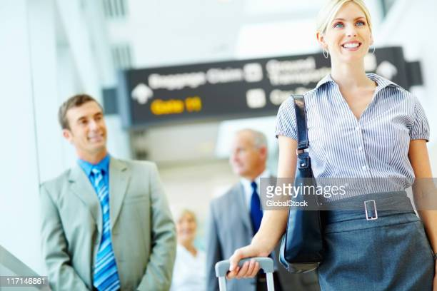 Jeune femme d'affaires avec les gens en arrière-plan à l'aéroport