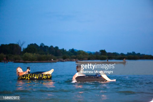 Travelers relax in tubes and take in the sunset : Stock Photo