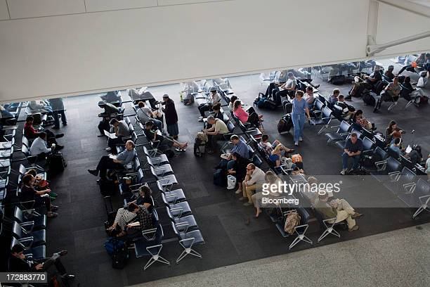 Travelers sit in a departure lounge at Toronto Pearson International Airport in Toronto Ontario Canada on Wednesday July 3 2013 Air Canada predicted...
