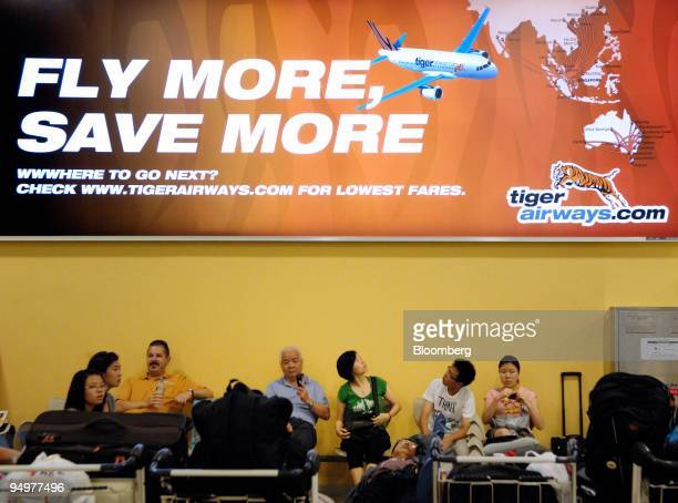 Travelers sit under a billboard advertising Tiger Airways Holdings Pte in the Budget Terminal at Changi Airport in Singapore on Sunday Dec 20 2009...