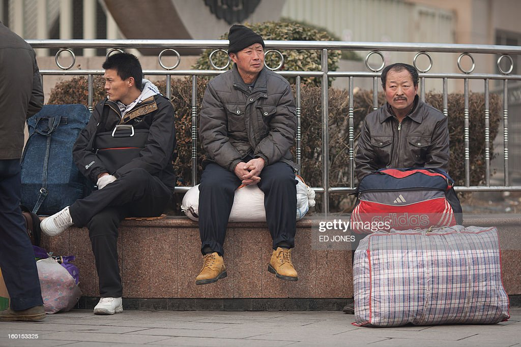 Travelers sit with their luggage at Beijing Railway Station in Beijing on January 27, 2013. The world's largest annual migration began in China with tens of thousands in the capital boarding trains to journey home for next month's Lunar New Year celebrations. AFP PHOTO / Ed Jones