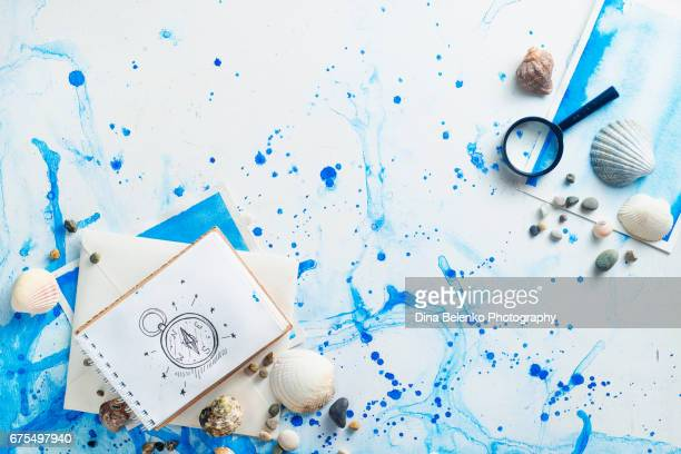 Travelers sketchbook with simple compass drawing on a wooden background with seashells