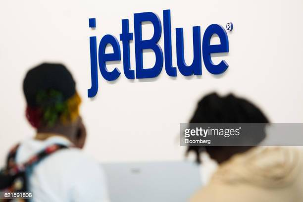 Travelers stand in front of JetBlue Airways Corp signage at Terminal 5 inside John F Kennedy International Airport in New York US on Wednesday July...