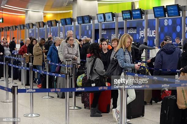Travelers stand in line in Terminal C at Logan International Airport attempting to get out ahead of the massive storm due to hit the northeast this...