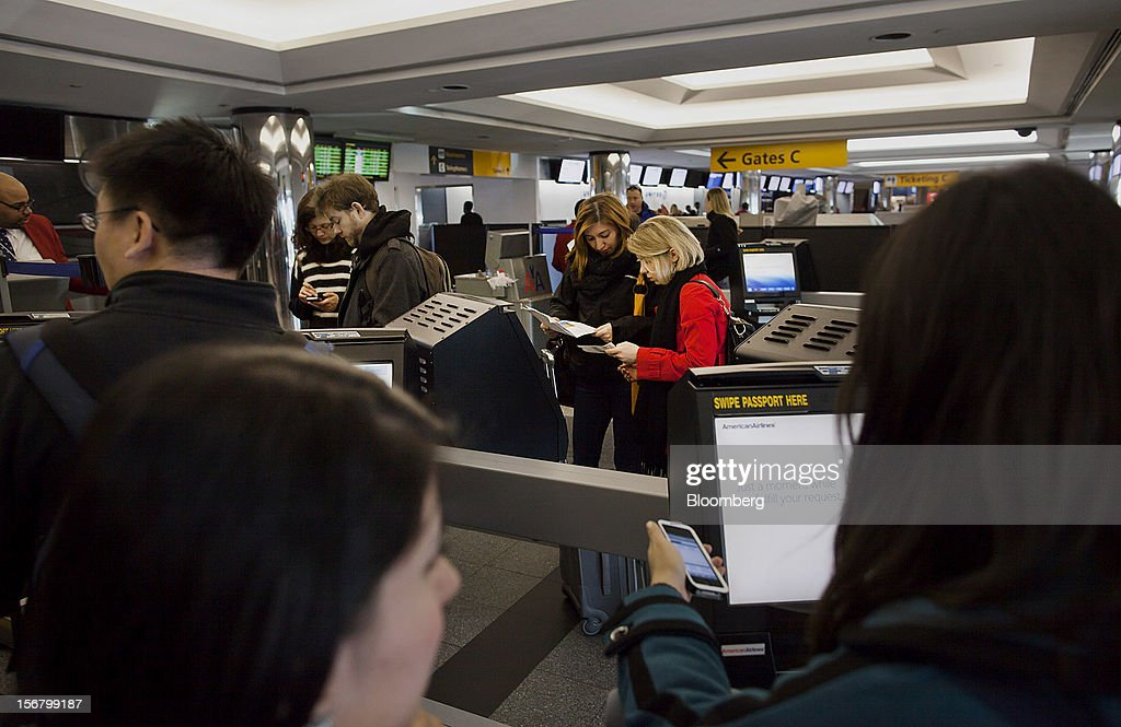 Travelers use American Airlines Inc. self-service kiosks to check in at LaGuardia Airport in the Queens borough of New York, U.S., on Wednesday, Nov. 21, 2012. U.S. travel during the Thanksgiving holiday weekend will rise a fourth straight year, gaining 0.7 percent from 2011, as trips by automobile rise even as airplane trips decline, AAA said last week. Photographer: Michael Nagle/Bloomberg via Getty Images
