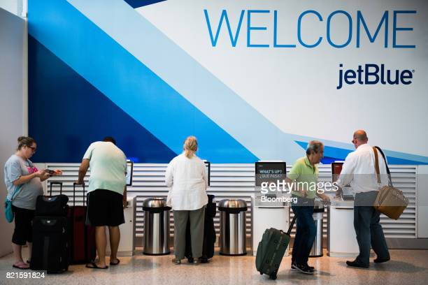 Travelers use the self checkin kiosks inside the JetBlue Airways Corp Terminal 5 at John F Kennedy International Airport in New York US on Wednesday...
