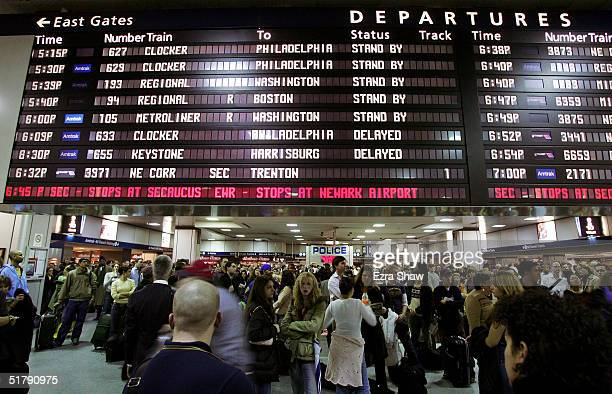 Travelers wait and watch the departures board at the Amtrak part of Penn Station on November 24 2004 in New York City Travelers across the country...