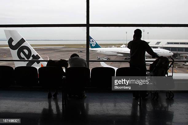 Travelers wait in a departure lounge as a Jetstar Airways aircraft left and an Air New Zealand Ltd aircraft stand on the tarmac at Auckland...