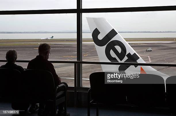 Travelers wait in a departure lounge as a Jetstar Airways aircraft stands on the tarmac at Auckland International Airport in Auckland New Zealand on...
