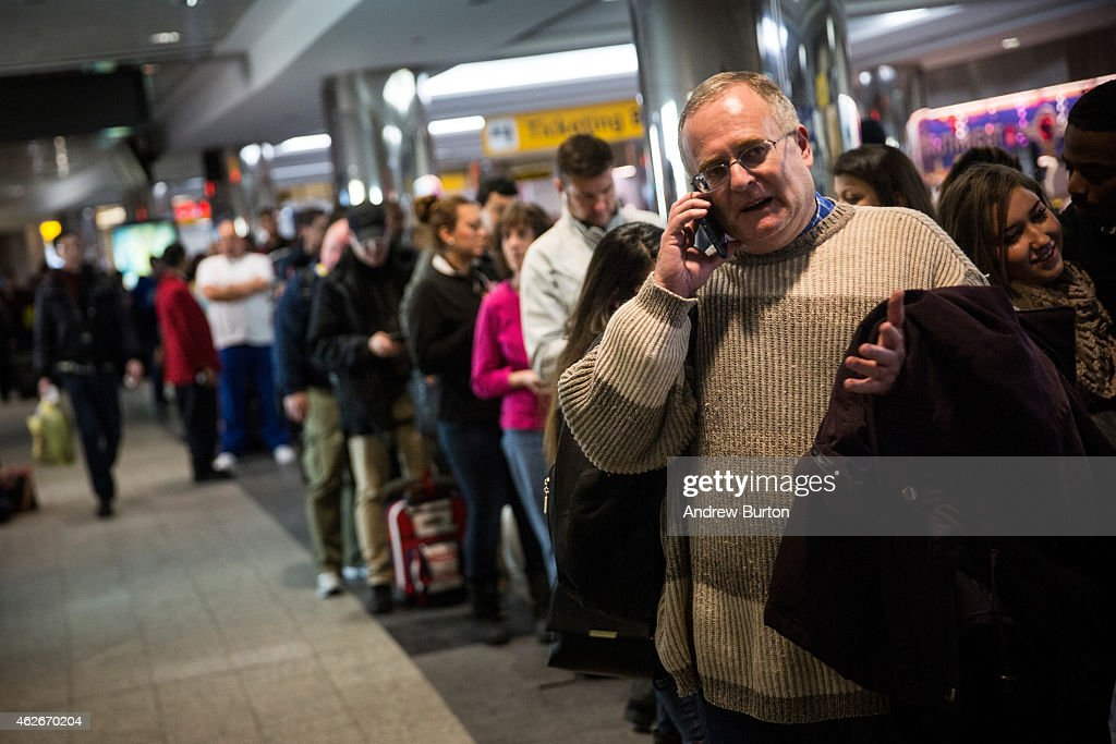 Travelers wait in a line at La Guardia Airport during a winter storm on February 2 2015 in the Queens borough of New York City The snowstorm which is...