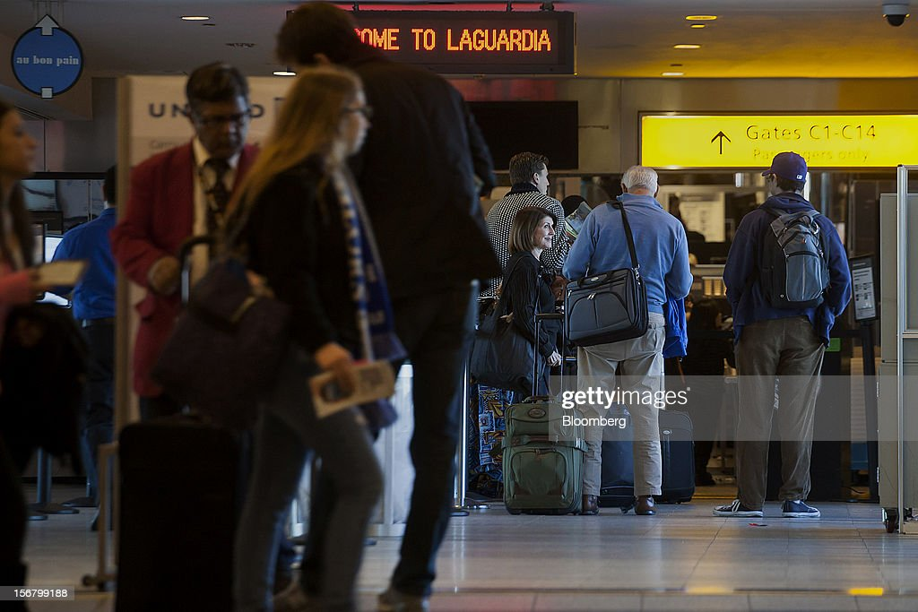 Travelers wait in a line to go through security at LaGuardia Airport in the Queens borough of New York, U.S., on Wednesday, Nov. 21, 2012. U.S. travel during the Thanksgiving holiday weekend will rise a fourth straight year, gaining 0.7 percent from 2011, as trips by automobile rise even as airplane trips decline, AAA said last week. Photographer: Michael Nagle/Bloomberg via Getty Images