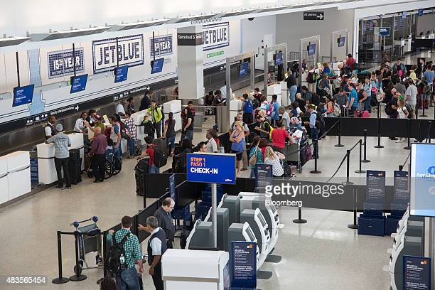 Travelers wait in line at JetBlue Airways Corp's Terminal 5 at John F Kennedy International Airport airport in New York US on Friday Aug 7 2015 The...