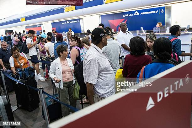 Travelers wait in line at the Delta checkin counter at LaGuardia Airport August 8 2016 in the Queens borough of New York City Delta flights around...